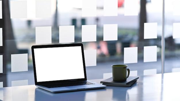 Verspotten sie laptop-computer mit leerem weißem bildschirm und kaffeetasse auf einfachem arbeitsplatz.
