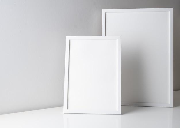 Verspotten sie moderne weiße plakatrahmen auf weißem tisch und betonwand