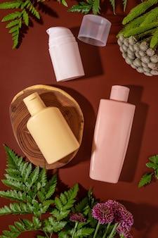 Verspotten sie naturkosmetik: serum, creme, maske für die werbung auf braunem hintergrund mit blumen. organische produkte. flache lay-komposition mit osmetischen flaschen.