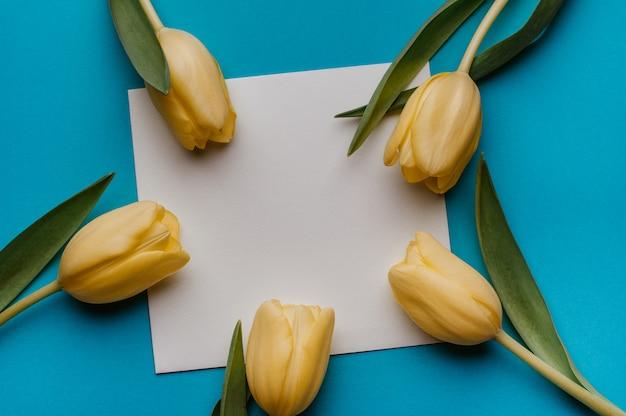 Verspotten sie oben mit gelben tulpen auf blau. flach liegen. frühling, muttertag konzept.