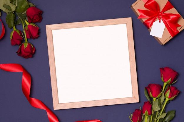 Verspotten sie sich für den valentinstag - leeren rahmen mit roten rosen und geschenk.