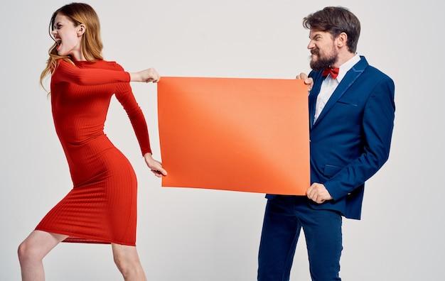 Verspotten sie sich in den händen einer frau in einem roten kleid und eines emotionalen mannes in einem anzug. hochwertiges foto