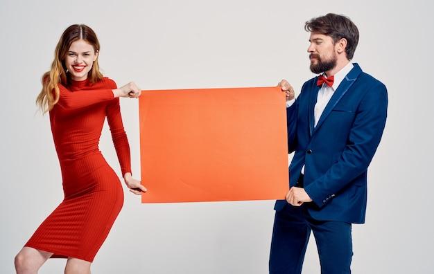Verspotten sie sich in den händen einer frau in einem roten kleid und eines emotionalen mannes in einem anzug