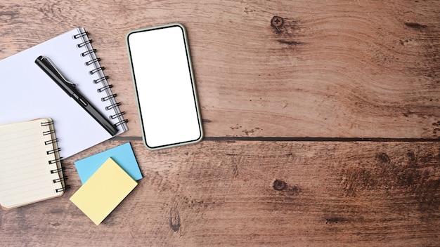 Verspotten sie smartphone, haftnotizen und notizbuch auf holzschreibtisch.