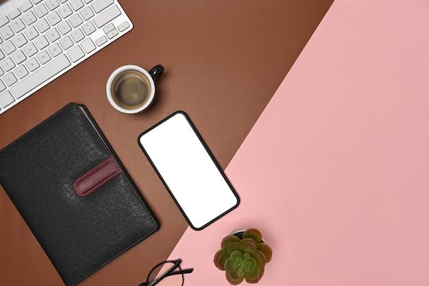 Verspotten sie smartphone, kaktus, notizbuch und brille auf zweifarbigem braunem und rosa hintergrund.