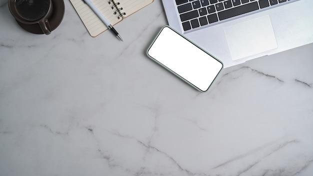 Verspotten sie smartphone mit leerem bildschirm und laptop-computer auf marmorhintergrund.