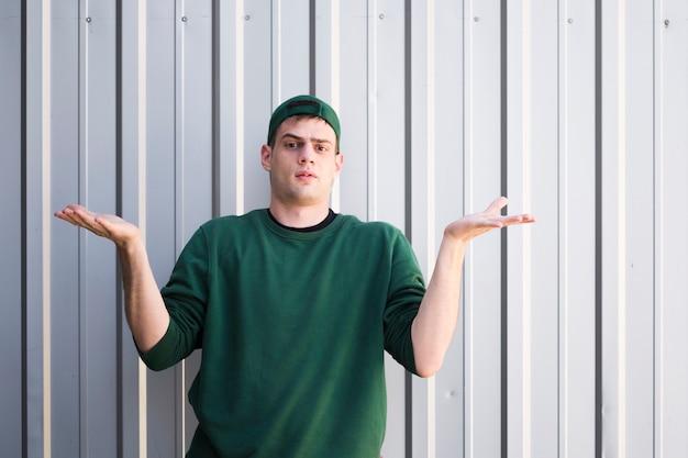 Verständnisloser junger kurier mit erhobenen händen