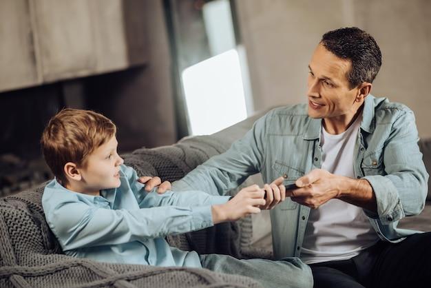 Verständnismangel. strenger junger vater, der seinen söhnen das telefon aus den händen nimmt und versucht, das spielen zu beenden, während der junge sich widersetzt