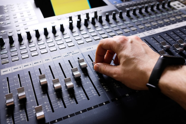 Verstärkungsgerät, das die studioknöpfe und fader des audiomischers anpasst. arbeitsplatz und ausrüstung des toningenieurs. akustisches mischen von musik