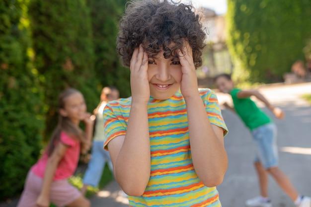 Versteck spiel. lächelnder junge mit dunklem lockigem haar in gestreiftem t-shirt, das das gesicht mit palmen bedeckt und energische freunde hinter seinem rücken im park versteckt