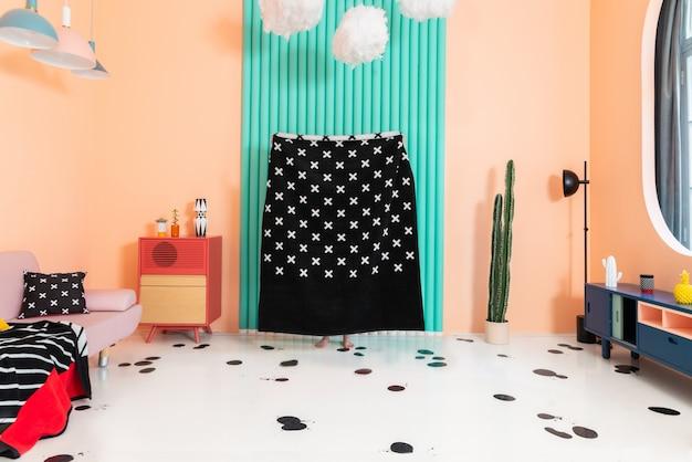 Verstecken spielen und spaß mit plaid zu hause haben, während sie sich in einem schlafzimmer mit farbenfrohen akzenten und geometrisch gemusterten textilien selbst isolieren.