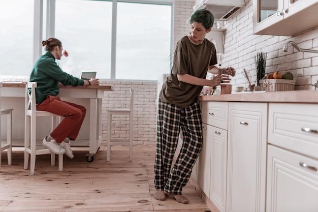 Verstecken vor dem menschen. freundin im pyjama versteckt sich vor ihrem mann und trinkt morgens alkohol