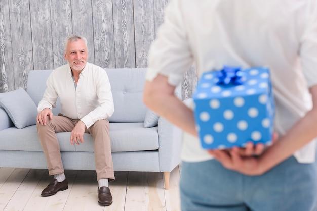 Versteckende geschenkbox der frau hinter ihr zurück vor ihrem glücklichen ehemann, der auf sofa sitzt