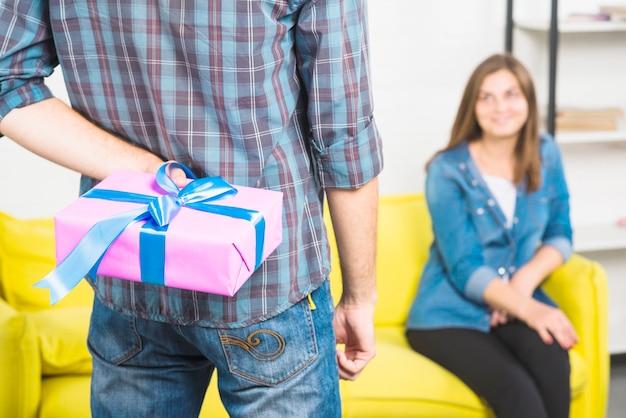Versteckende geschenkbox des mannes hinter seinem zurück vor der freundin, die auf sofa sitzt