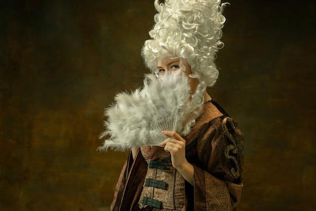 Versteckt sich mit flauschigem fächer. porträt der mittelalterlichen jungen frau in der braunen weinlesekleidung auf dunklem hintergrund. weibliches modell als herzogin, königliche person. konzept des vergleichs von epochen, modern, mode, schönheit.