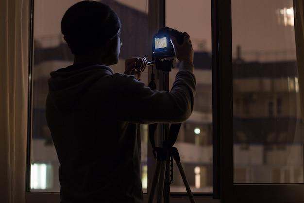 Versteckte paparazzi schießen nachts aus dem fenster auf der anderen straßenseite auf ein ziel