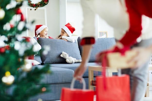 Versteckte töchter, die ihre eltern beobachten, legen weihnachtsgeschenke unter den baum