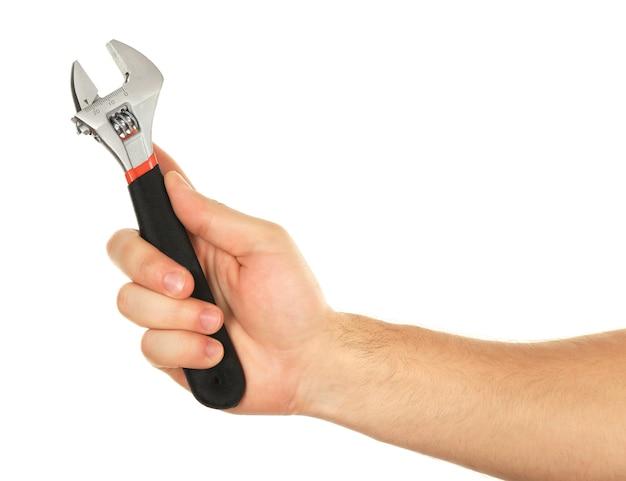 Verstellbarer schraubenschlüssel in männlicher hand lokalisiert auf weiß