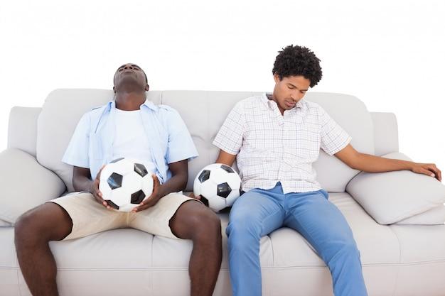 Verstörte fußballfans, die auf der couch mit bällen sitzen