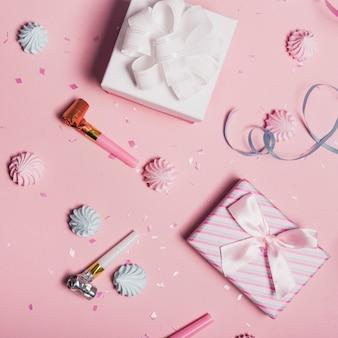Verstreut konfetti; schlagsahne und partygebläse mit geschenkboxen auf rosa hintergrund