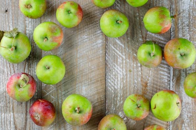 Verstreute äpfel auf holz. flach liegen.