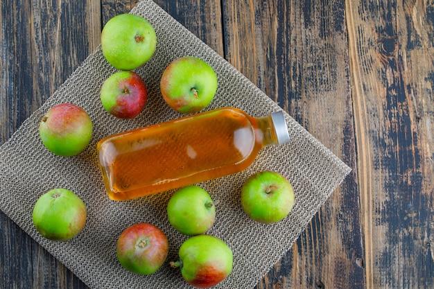 Verstreute äpfel mit flachem getränk lagen auf holz- und tischset-hintergrund