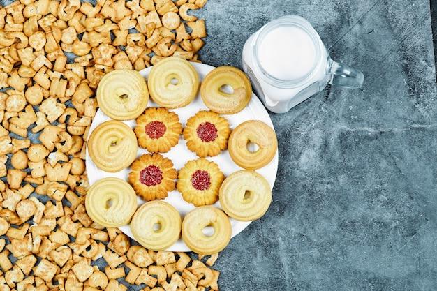 Verstreute alphabet-cracker, ein teller mit keksen und ein glas milch auf einem marmortisch.