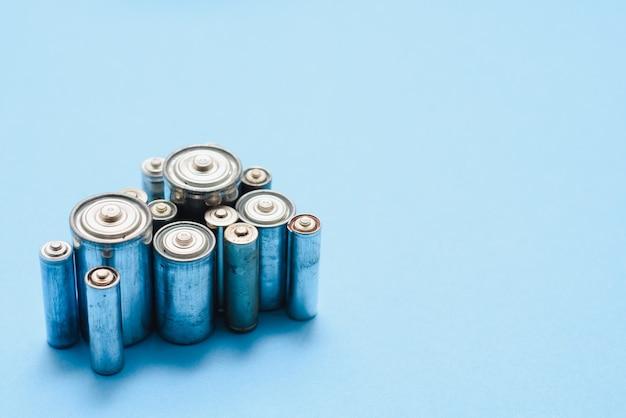 Verstreute alte schmutzige batterien aa oder aaa größe auf blauem hintergrund