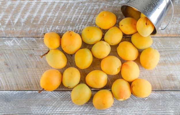 Verstreute aprikosen aus einem kleinen eimer auf einem holztisch. flach liegen.