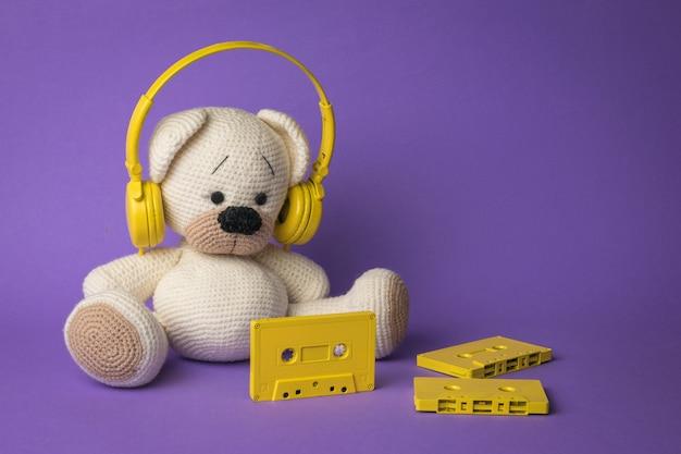 Verstreute bandkassetten und ein gestrickter bär mit kopfhörern auf violettem hintergrund. das konzept der behandlung von krankheiten.