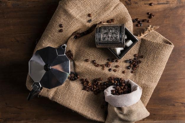 Verstreute bohnen aus sack in der nähe von kaffeemaschine und schachtel zucker