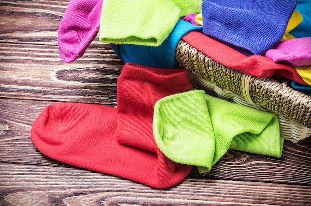 Verstreute bunte socken und wäschekorb