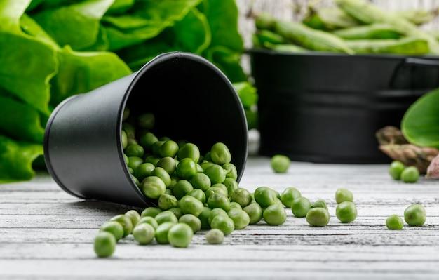 Verstreute erbsen aus einem eimer mit spargel, bok choy, salat, seitenansicht der grünen schoten auf einer holzwand