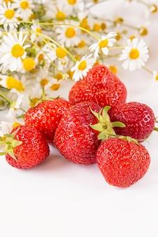 Verstreute erdbeeren mit einem strauß kamillenblüten. sommer beerensaison.