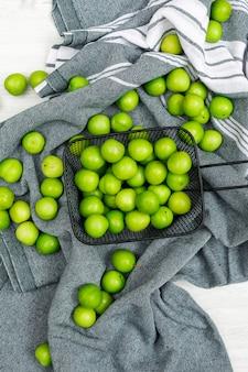Verstreute grüne pflaumen in einem schwarzen cullender auf einem küchentuch und weißem holz. flach liegen.