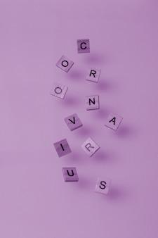 Verstreute holzbuchstaben in form des wortes coronavirus lila