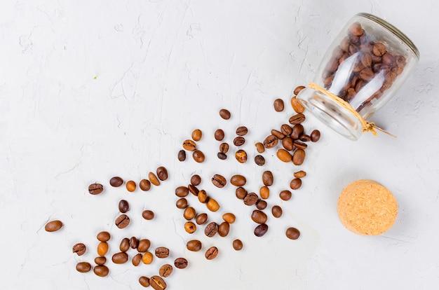 Verstreute kaffeebohnen aus einem glas