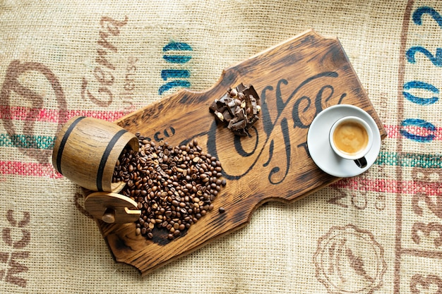 Verstreute kaffeebohnen, eine tasse espresso, schokoladenstücke mit nüssen auf einem holzbrett.