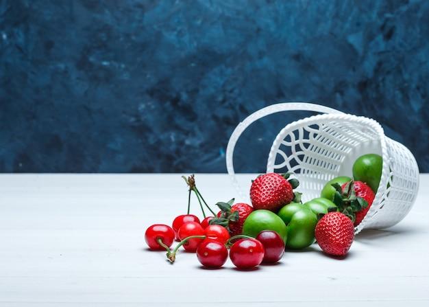 Verstreute kirschen mit erdbeeren und grünen pflaumen aus einem korb