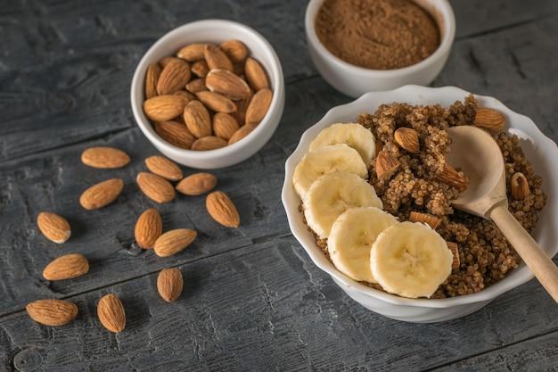 Verstreute mandeln, quinoa-brei mit banane auf einem rustikalen tisch. gesunde ernährung. flach liegen.