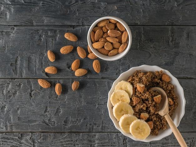 Verstreute mandeln, quinoa-brei mit banane auf einem schwarzen rustikalen tisch. gesunde ernährung. flach liegen.