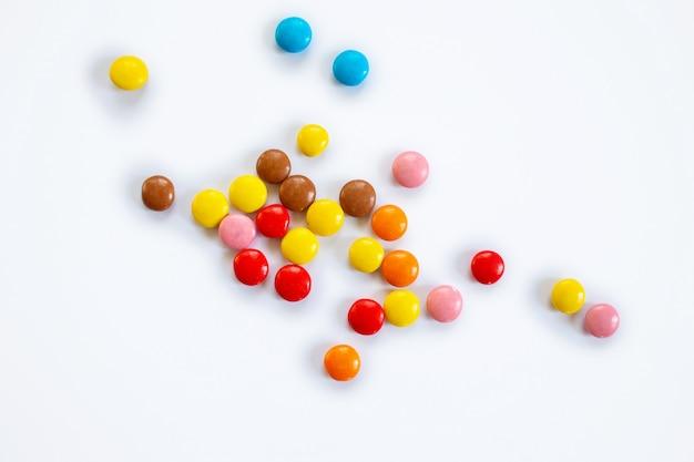 Verstreute mehrfarbige kleine runde süßigkeiten. schokoladendragees in der mehrfarbigen glasur auf einem weißen hintergrund