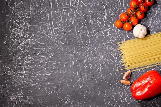 Verstreute nudeln, knoblauch, tomaten, auf grauem hintergrund