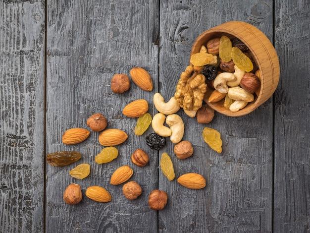 Verstreute nüsse und getrocknete früchte mit einer holzschale auf einem holztisch. natürliches gesundes vegetarisches essen.