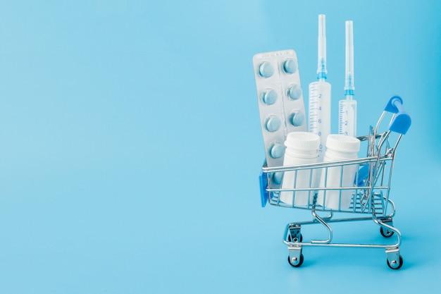 Verstreute pharmazeutische medizinpillen, tabletten und kapseln auf dollargeld isoliert auf blauer wand. medikamentenkosten.