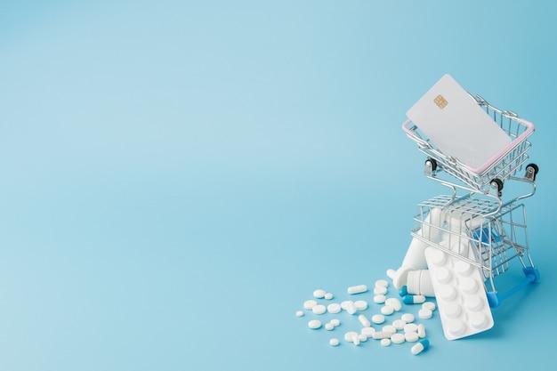 Verstreute pillen, drogen, spay, flaschen, thermometer, spritze und leerer einkaufswagen auf blauem hintergrund. apotheken-einkaufskonzept.