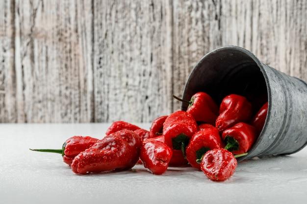 Verstreute rote paprika aus einem mini-eimer auf weißer und hölzerner schmutzwand, seitenansicht.