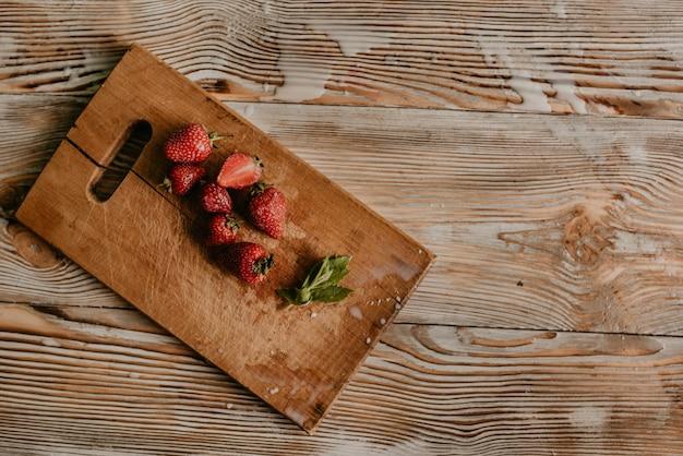 Verstreute saftige frische rote erdbeeren auf dem tisch mit vintage-planke. blatt minze. tropfen und spritzer verschütteter milch.