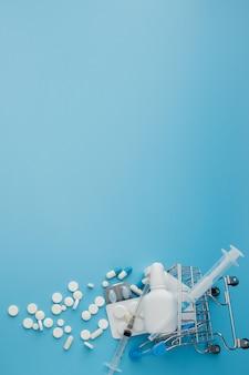 Verstreute sortenpillen, drogen, spay, flaschen, thermometer, spritze und leerer einkaufswagen auf blauem hintergrund. apothekeneinkaufskonzept