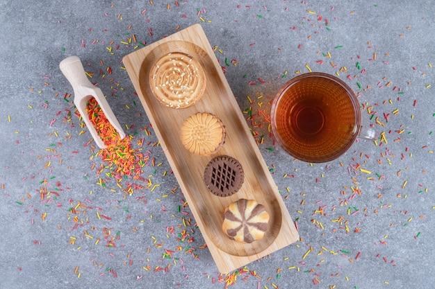 Verstreute süßigkeiten, eine kugel, eine tasse tee und verschiedene kekse